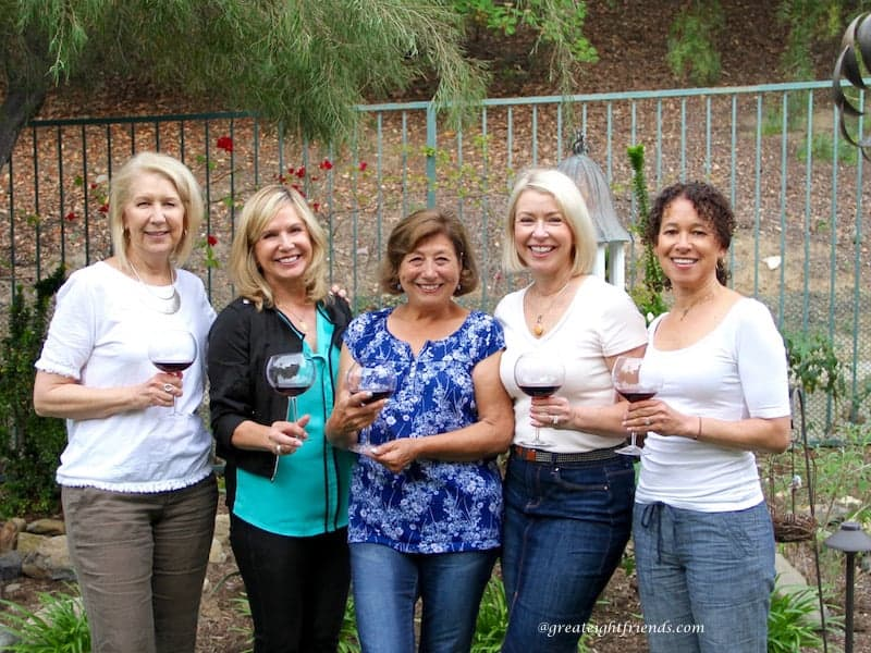 Five ladies drinking wine in the yard.