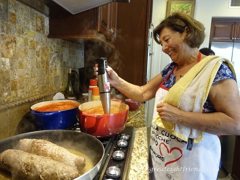 An Italian woman cooking red sauce and beef braciole at the stove using an immersion blender in one red pot.