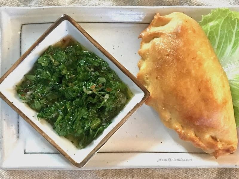 One chorizo empanadas on a small plate with a small side bowl of board dressing.