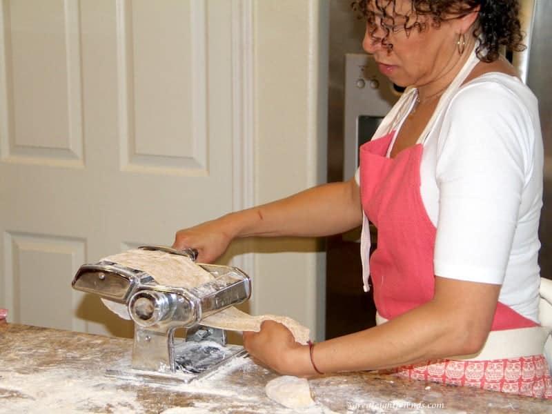 Debbie putting homemade pasta through a pasta maker.