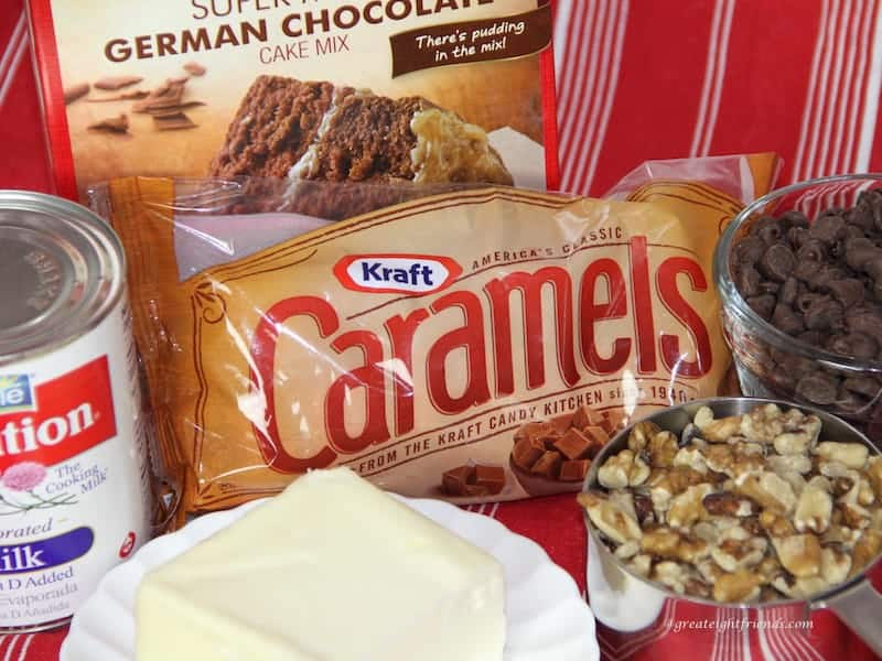 Ingredients to make brownies including cake mix, chocolate chips, bag of caramels, evaporated milk, butter and nuts.