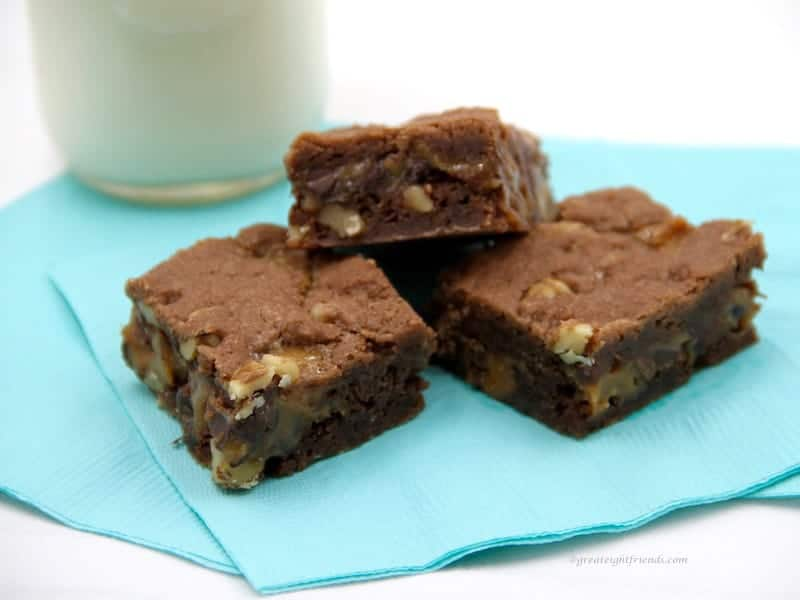 Three brownies sitting on a blue napkin with a glass of milk in the background.