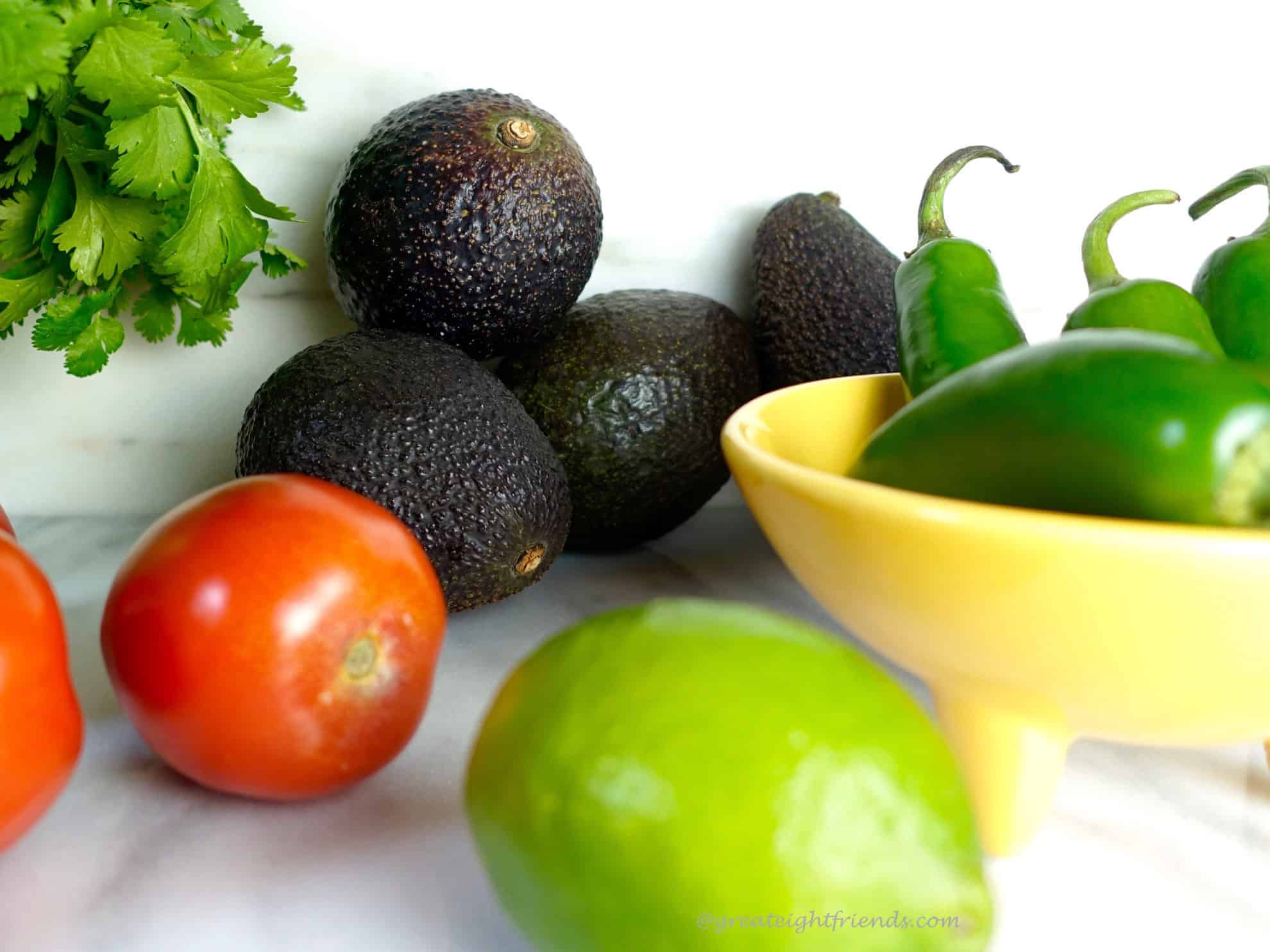 Avocados, cilantro, jalapenos in a yellow bowl, tomatoes and a lime.