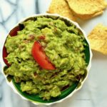Overhead shot of a bowl of guacamole topped with a wedge of tomato with tortilla chips scattered around.