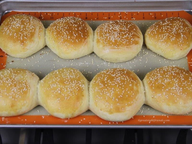 Baked homemade hamburger buns with sesame seeds on baking sheet