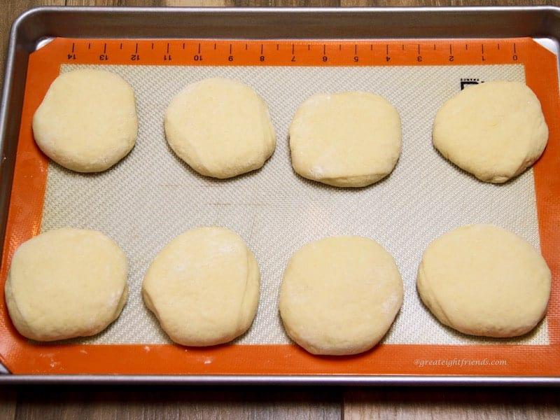 Unbaked buns on baking sheet rising
