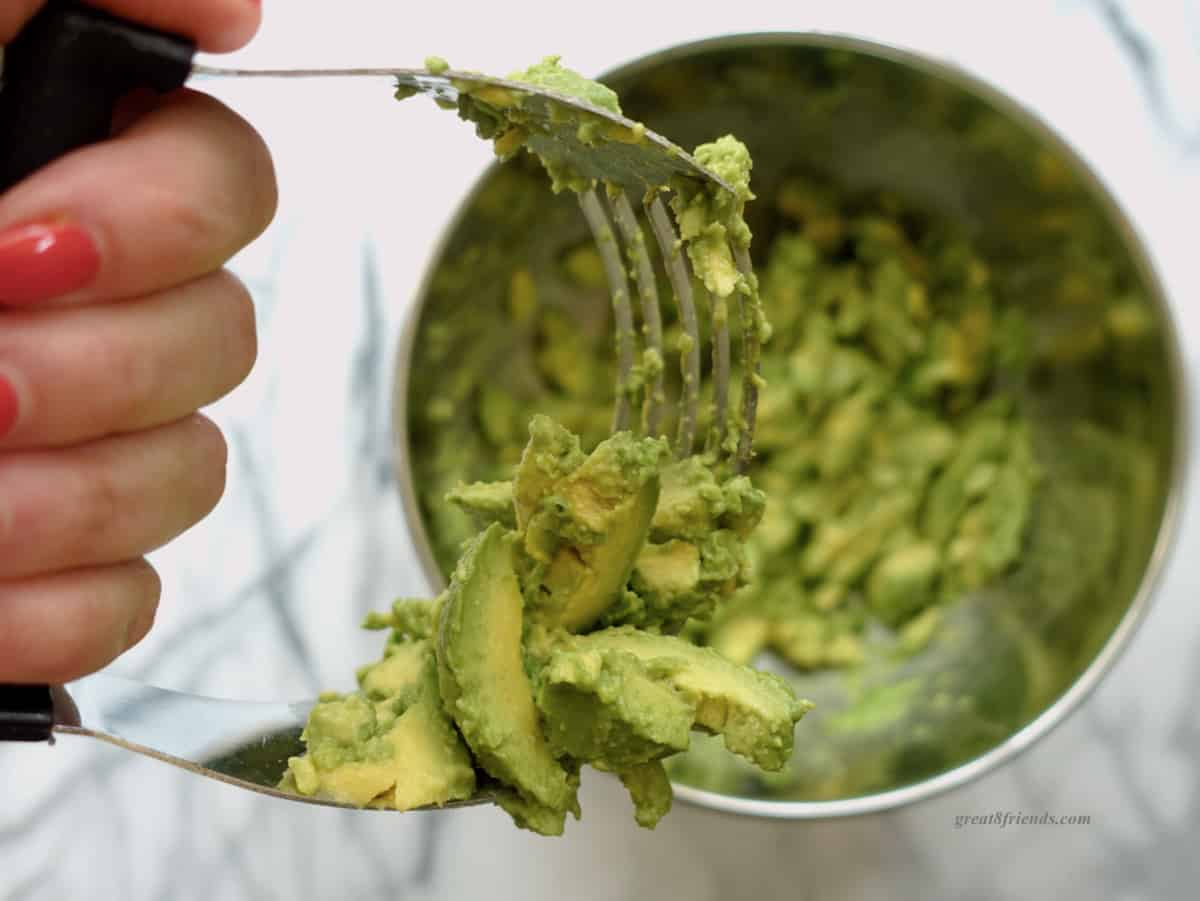 A hand holding a pastry cutter mashing avocados.