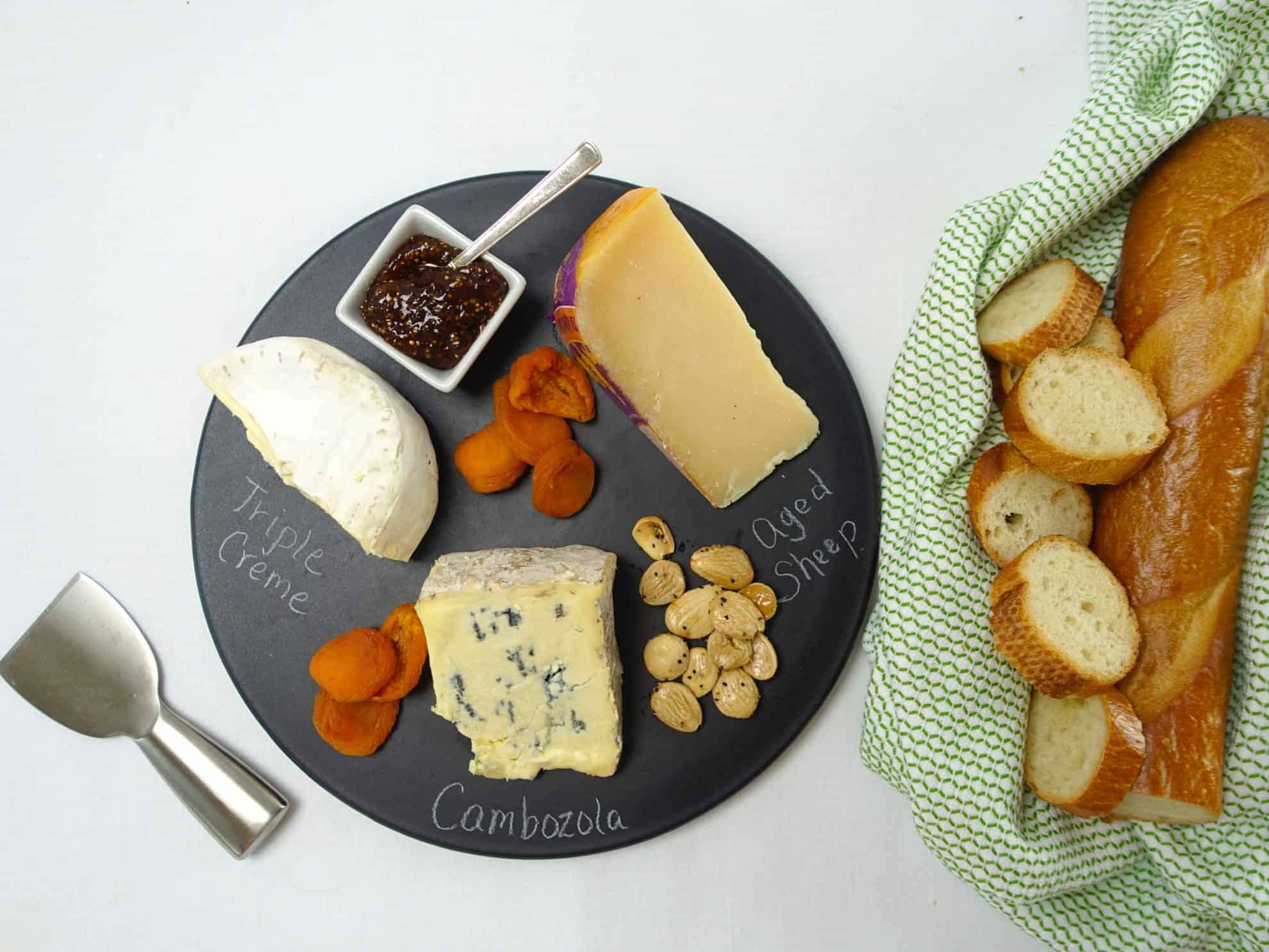A Cheese and Charcuterie Board with apricots, fig jam, almonds and bread slices.
