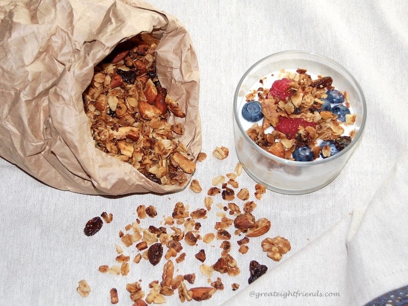 A brown paper sack with granola spilling out of it and a small glass bowl with yogurt and granola and berries in it.