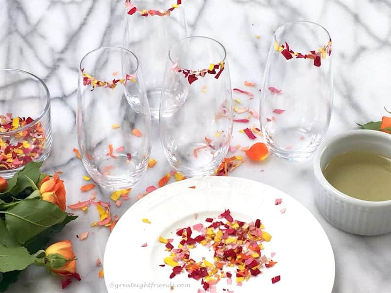 Edible flowers cut into confetti ready to rim stemless flute glasses.