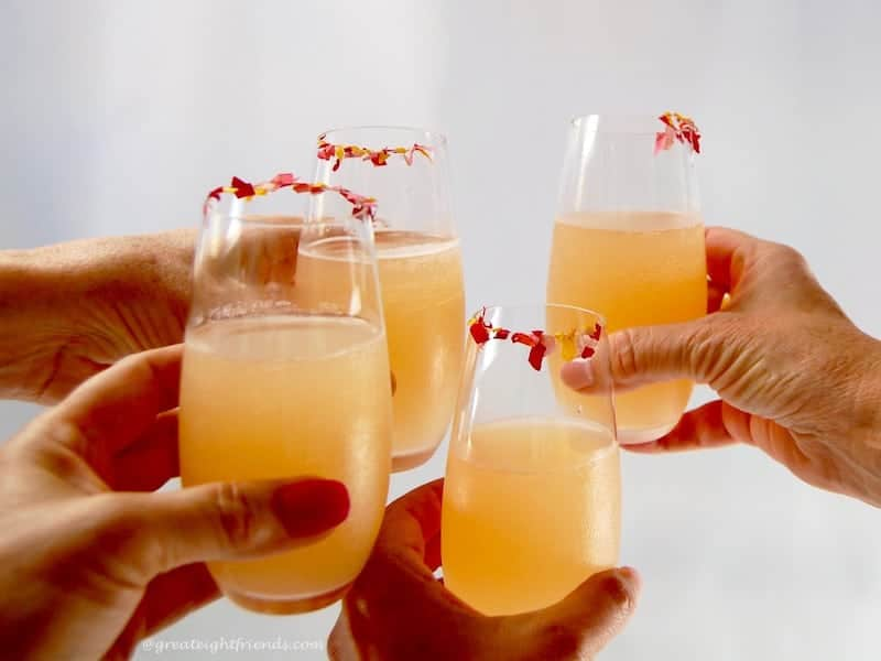Four Pink Lemonade Margaritas in stemless flutes toasting.