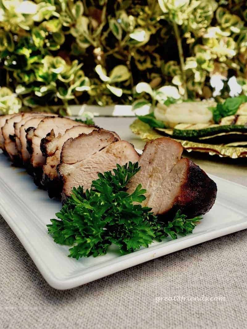 Sliced grilled pork tenderloin on a white plate with a parsley garnish.