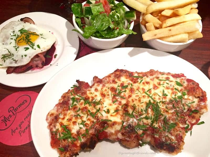 A white plate with chicken parma surrounded by fries and salad.