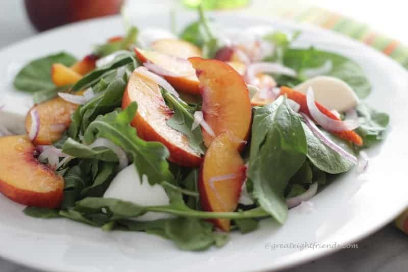Salad greens tossed with pickled nectarines and burrata cheese on a white plate.