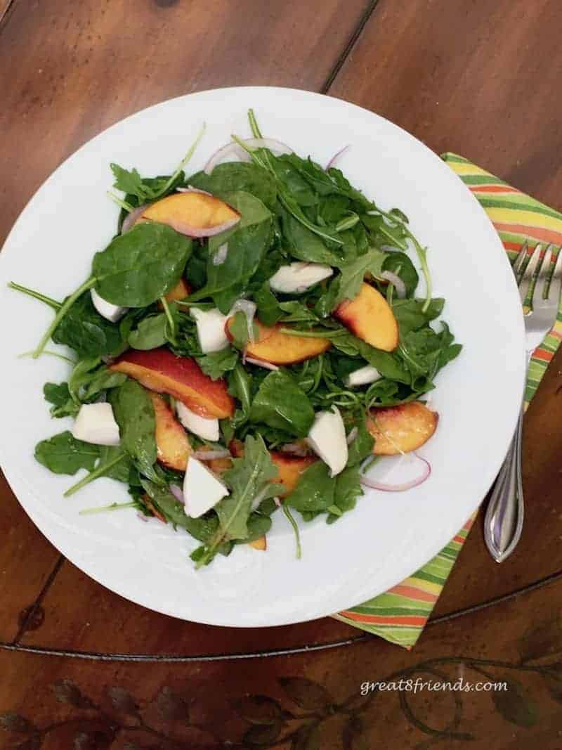 Overhead shot of green salad tossed with nectarines and burrata cheese. A fork is alongside the white salad plate.
