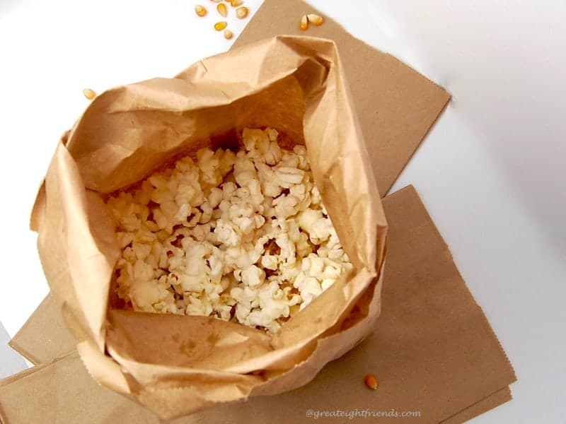 A brown paper bag filled with popped popcorn.