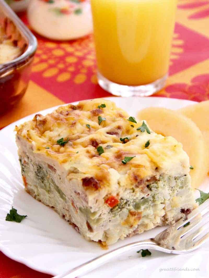Hash brown egg casserole served with sliced cantaloupe and orange juice.