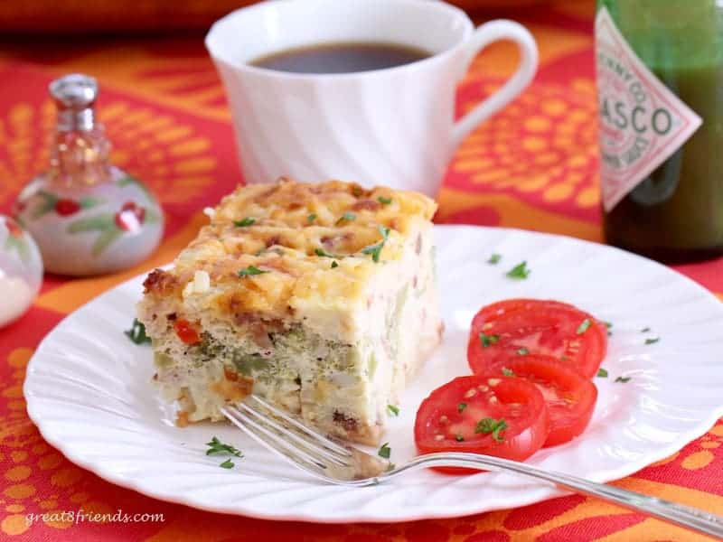 Hash brown egg casserole served with sliced tomatoes and a cup of coffee.