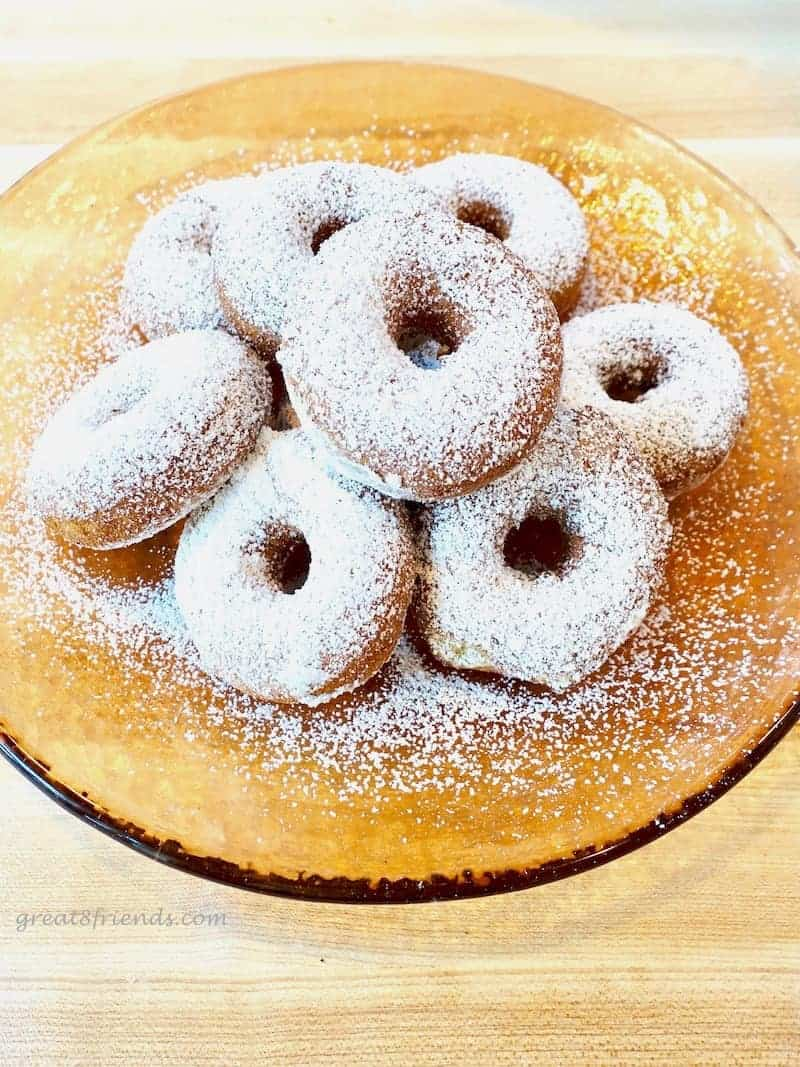 Overhead shot of a pile of donuts, covered with powdered sugar on an orange glass plate.