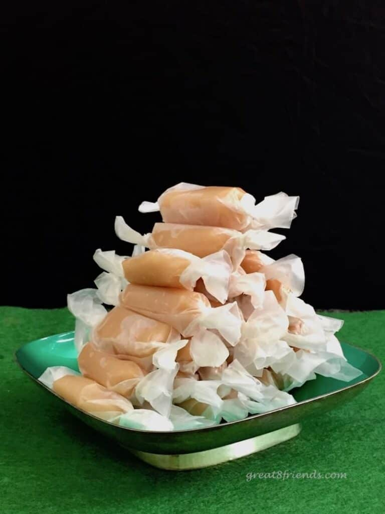 Creamy Caramels stacked in pyramid shaped on green dish on green felt