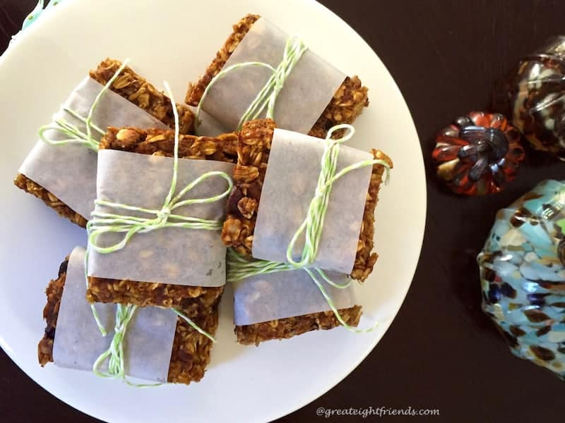 Pumpkin Granola Bars wrapped in parchment, tied with green twine and stacked on a plate.