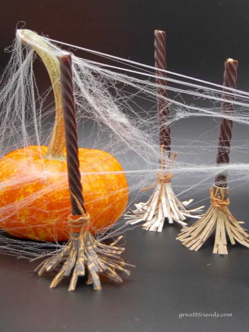 Three Witch's Brooms and one mini pumpkin with fake spider web all over.