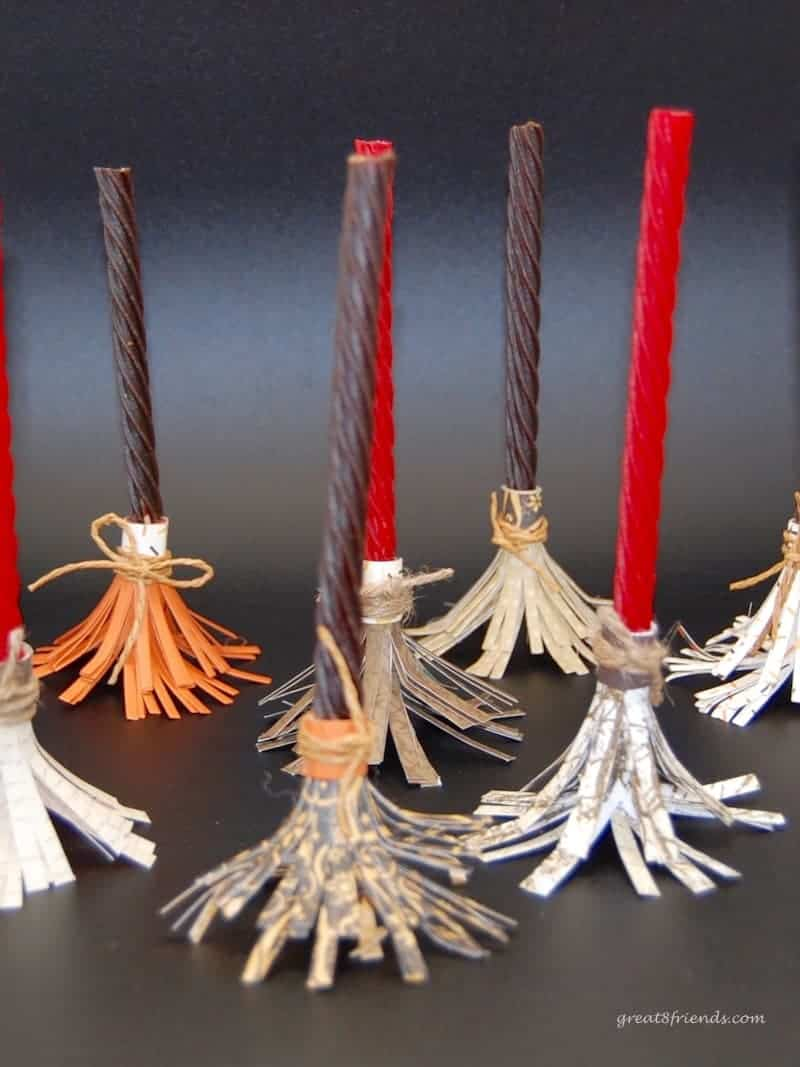 Several of the witch's brooms made from candy vines and paper standing up.