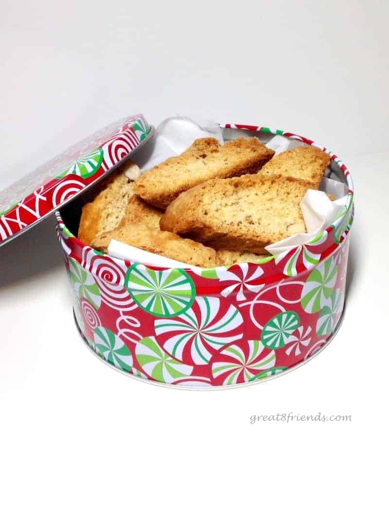 A round christmas tin stuffed with biscotti.