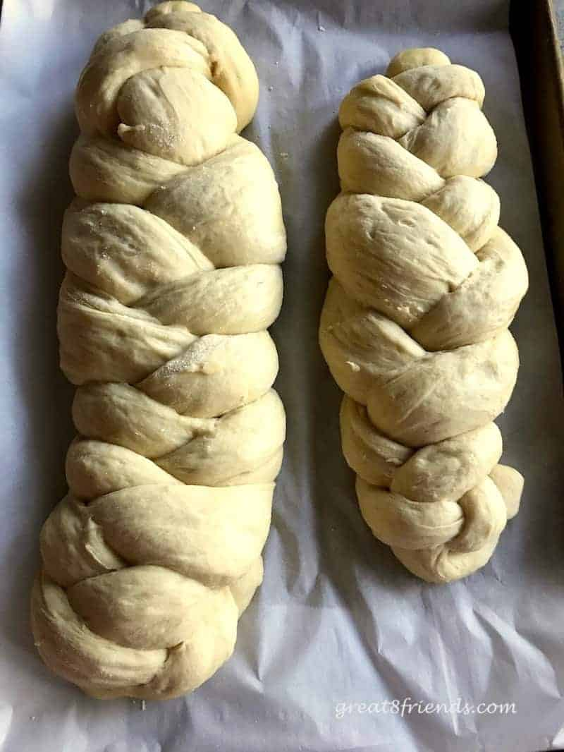 Two loaves of braided challah ready to be baked.