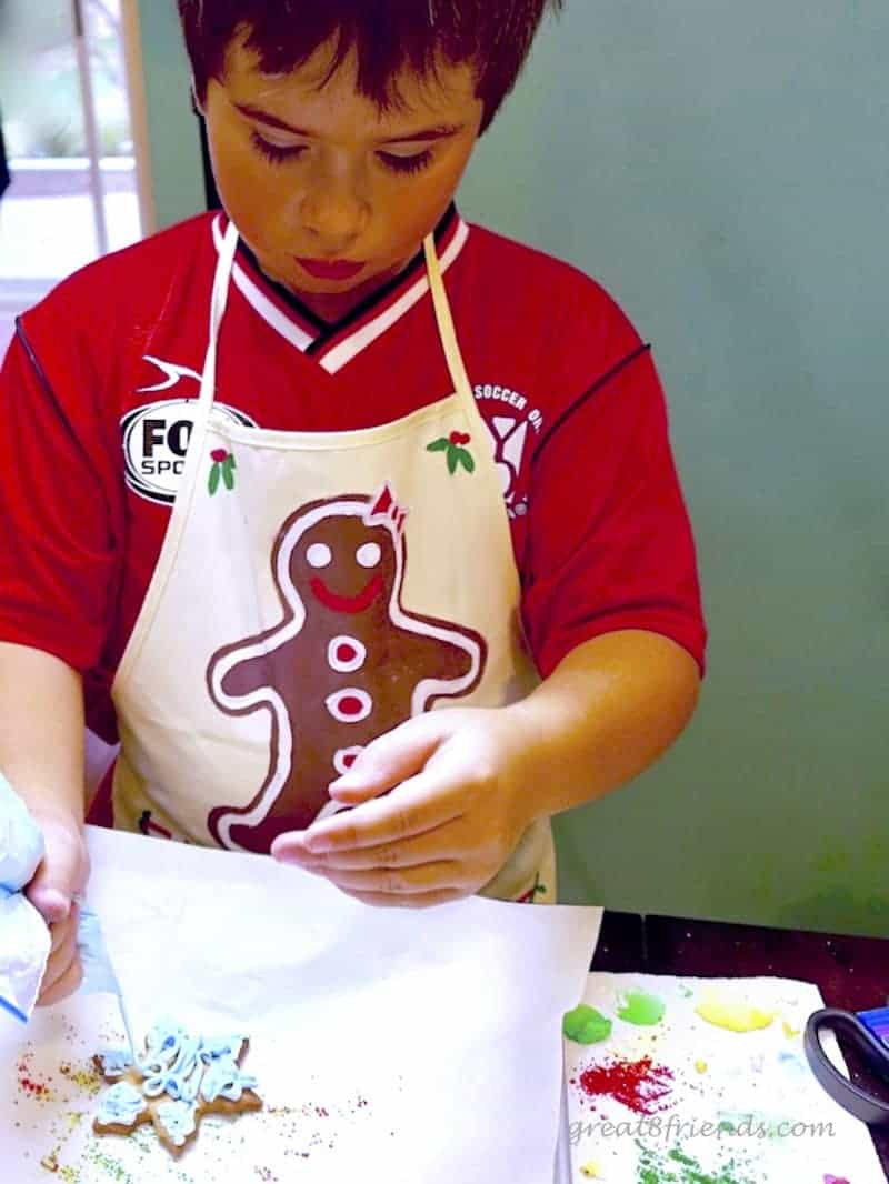 A child decorating a snowflake cookie.
