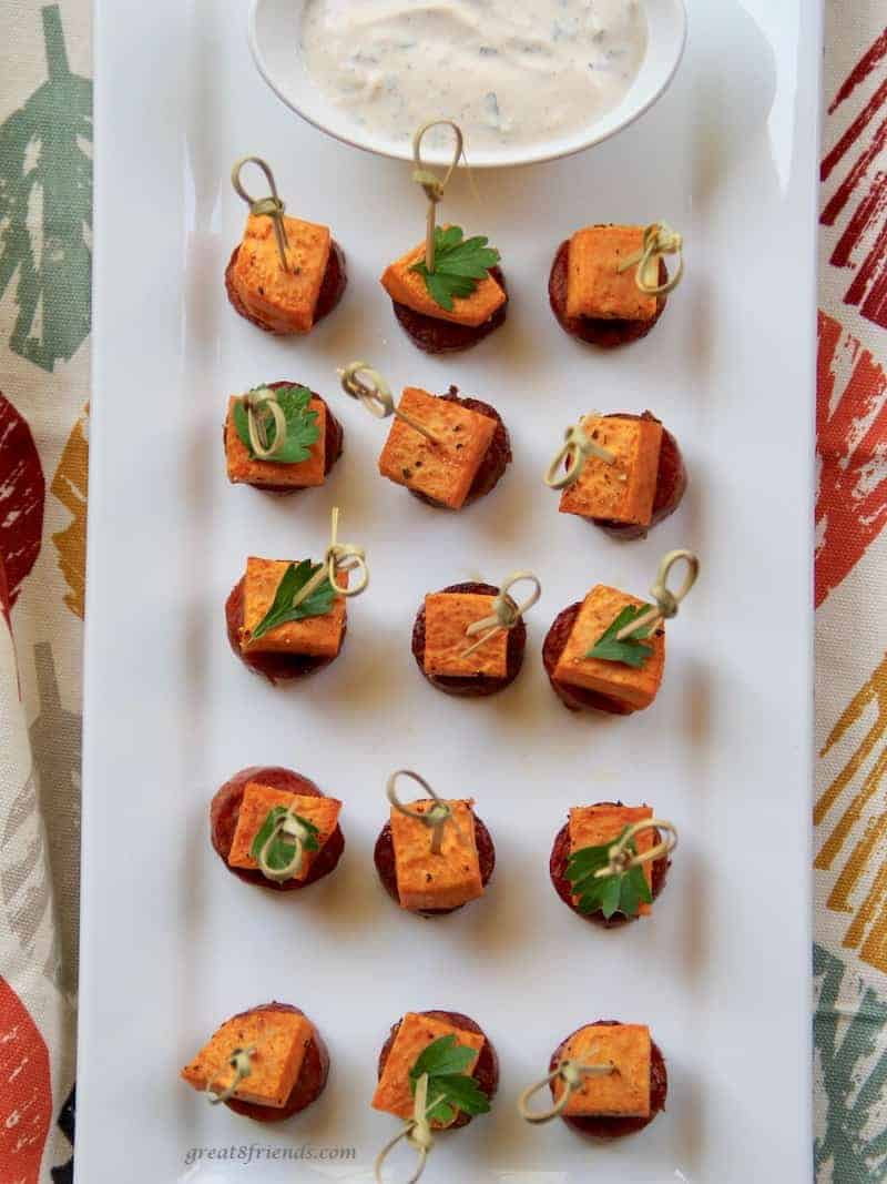 Several appetizer sticks on a white rectangular platter with a sweet potato piece and slice of sausage on the end.