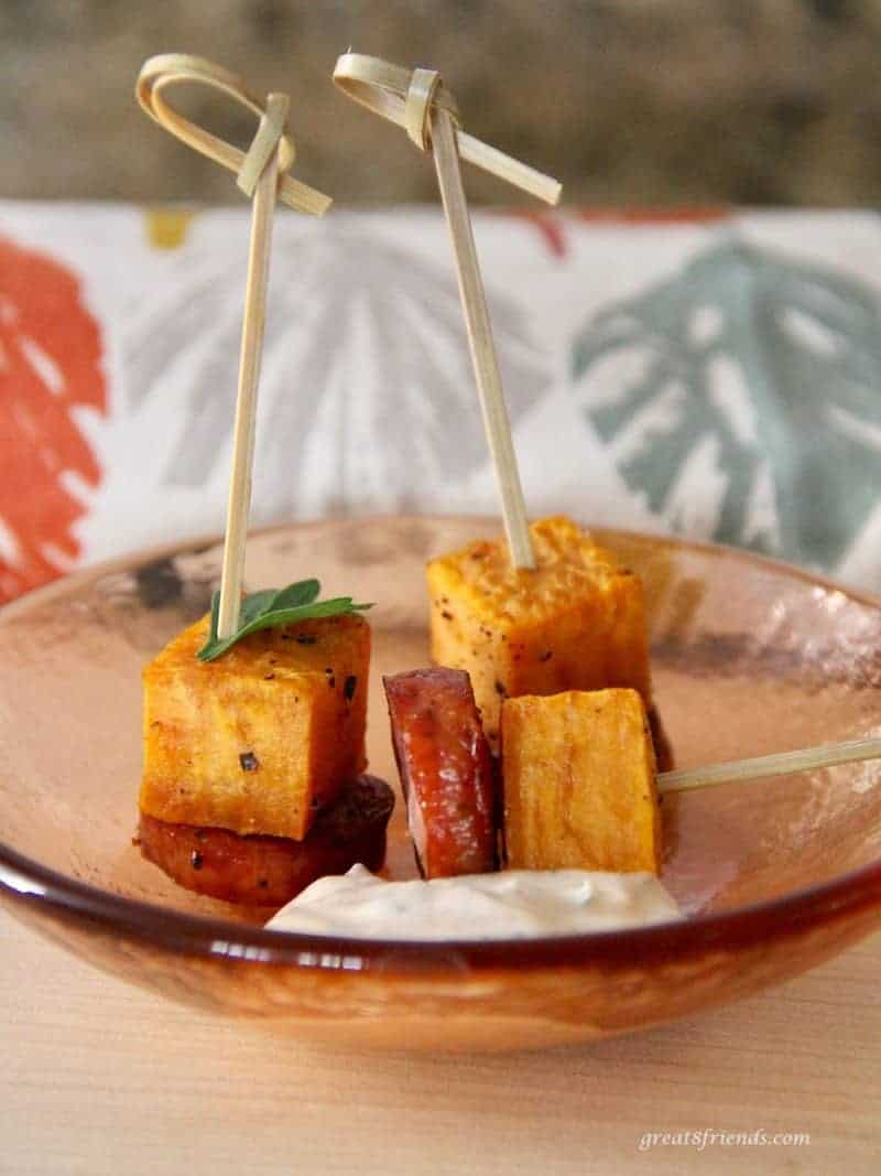 Three appetizer sticks with a small square of sweet potato and sausage on each.