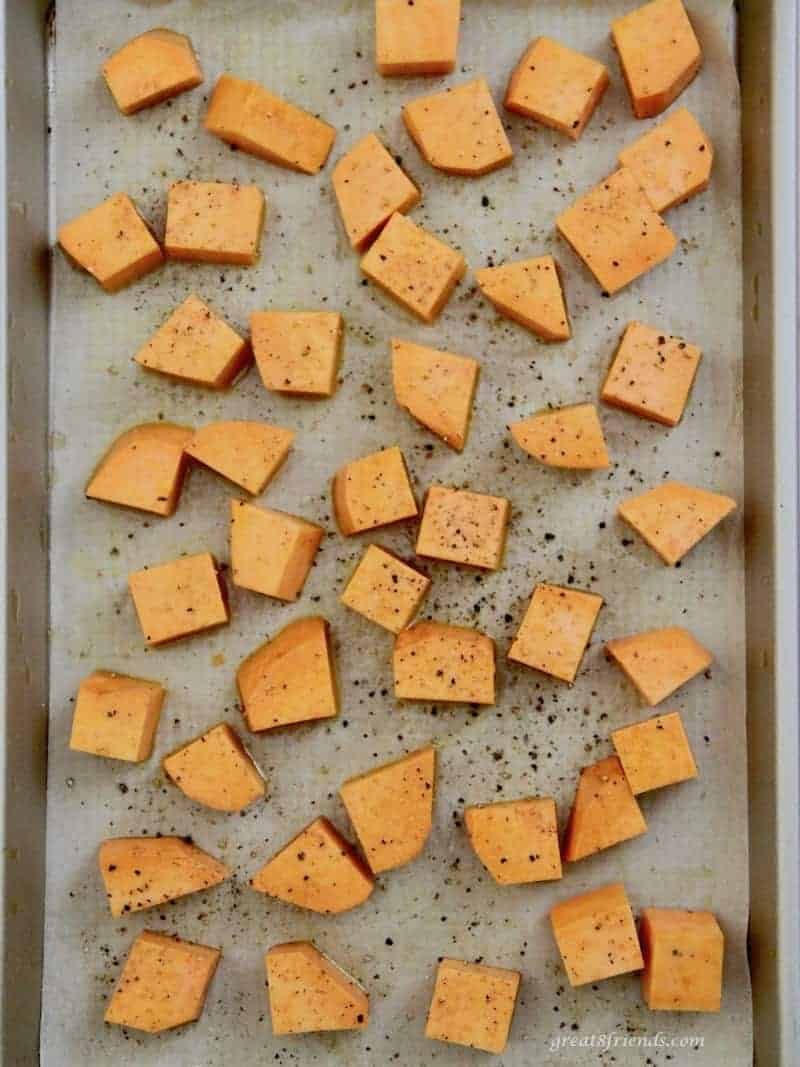 one inch squares of sweet potato sprinkled with pepper on a baking sheet.