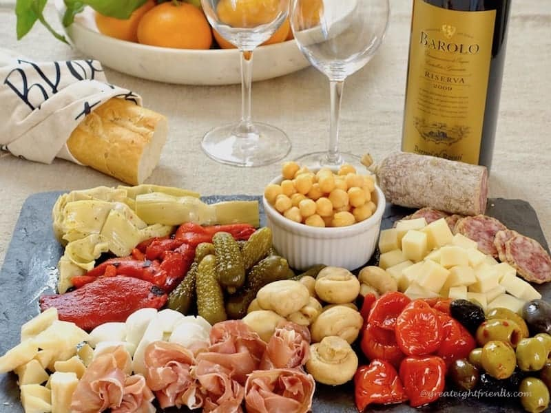 Antipasto platter with bread and wine.