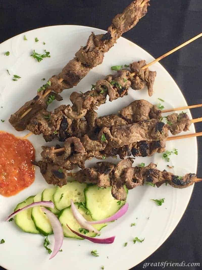beef satay skewers with sauce and cucumbers