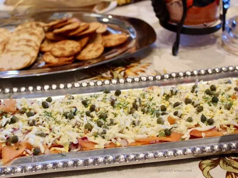 A decorative rectangular silver tray with smoked salmon layered dip with crackers in the background.