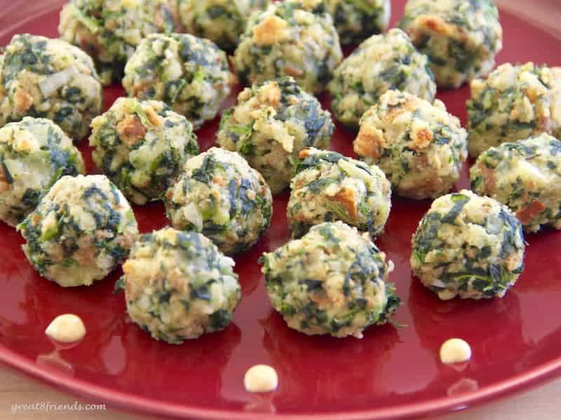 Spinach appetizer balls on a red plate.
