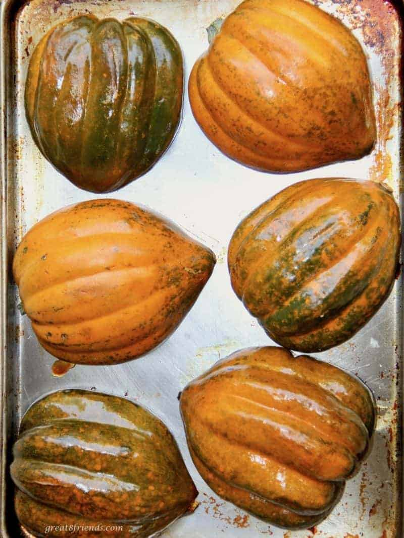 Acorn squash cut in half and laying cut side down on a baking sheet.