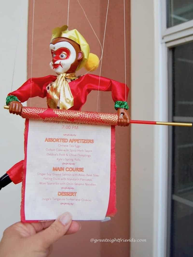 Chinese new year monkey marionette holding a scroll invitation.