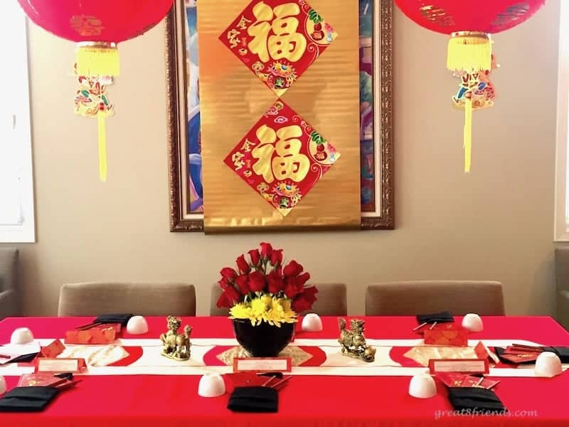 Table set for Chinese new year with paper lanterns hanging above.