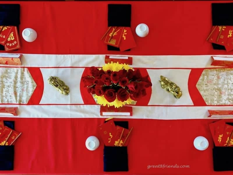Overhead shot of a table set for Chinese New Year with a red tablecloth, Asian style runner and rose centerpiece.