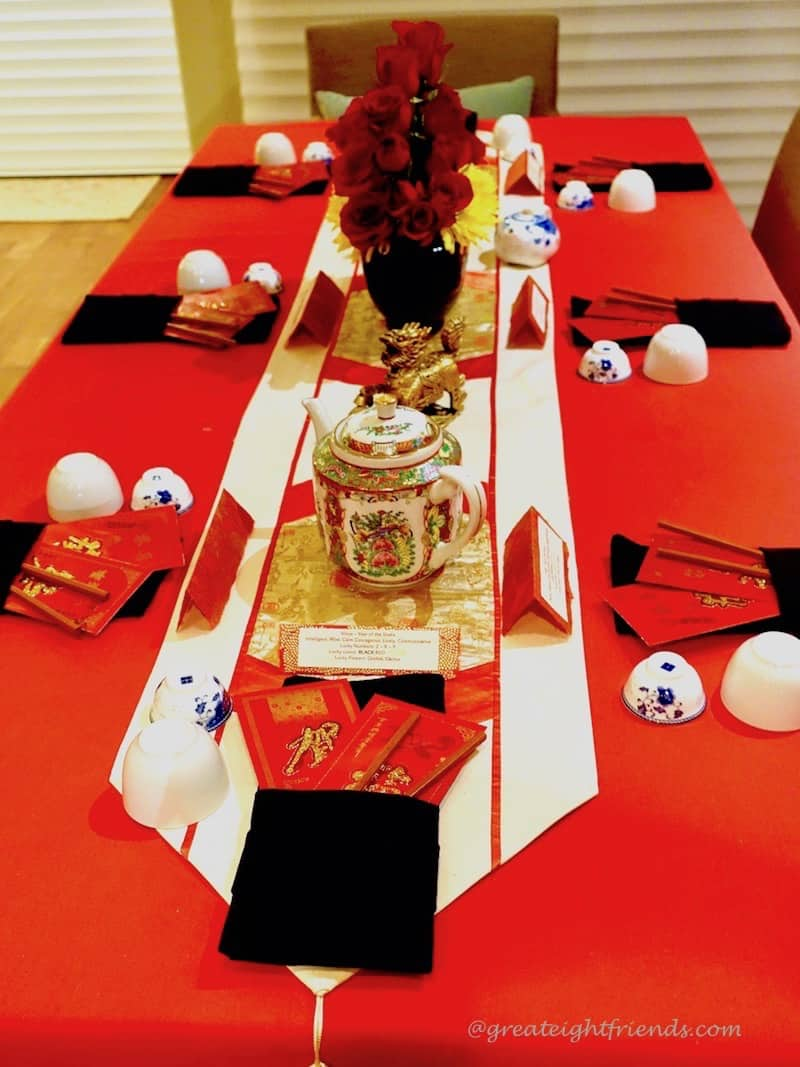 Chinese New Year Table setting with Chinese porcelain tea pot and red rose centerpiece.