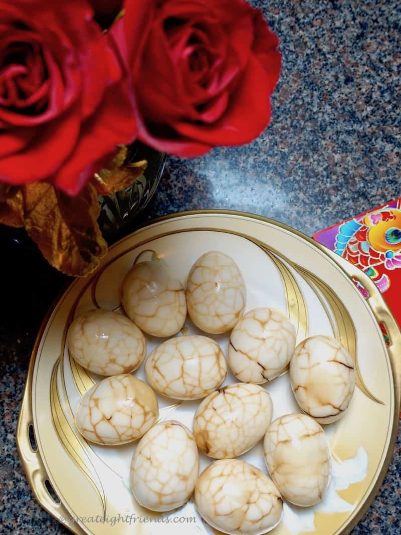 Chinese tea eggs on a gold and white plate.