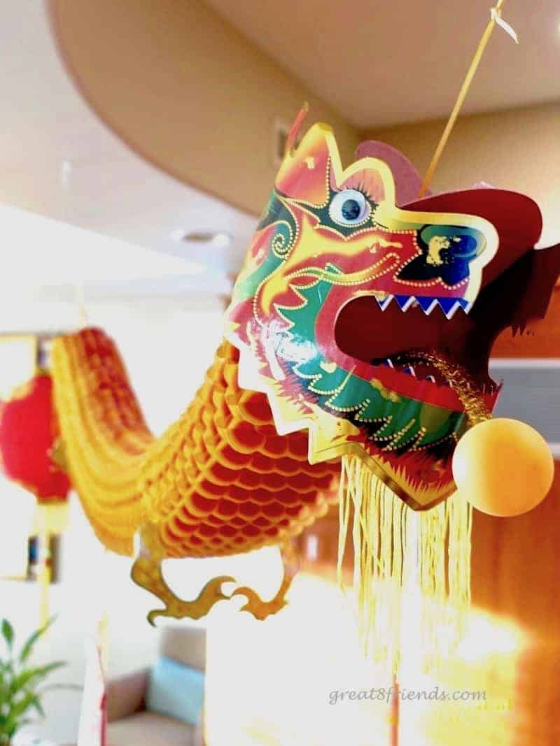 A colorful paper Chinese dragon hanging from a ceiling.