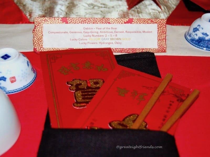 Chinese New Year place setting with red money envelopes and chopsticks.