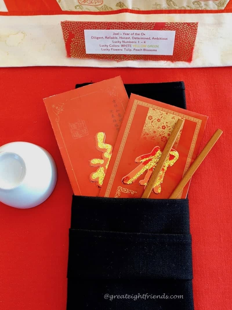 Lunar New Year place setting, a folded black napkin with red money envelopes and chopsticks.