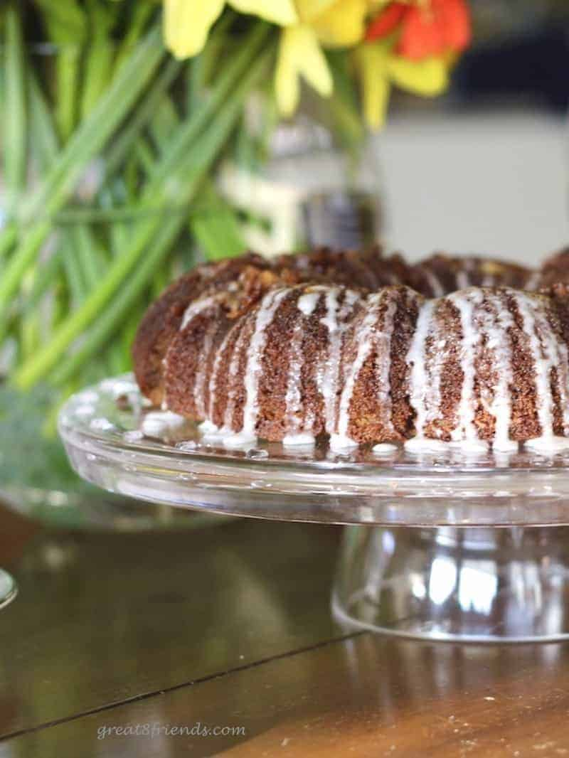 vertical image of gluten free cinnamon coffee cake with flowers behind.