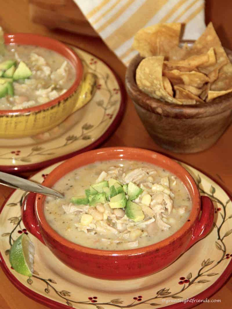 Two bowls of White Cheddar Chicken Chili and a bowl of tortilla chips.
