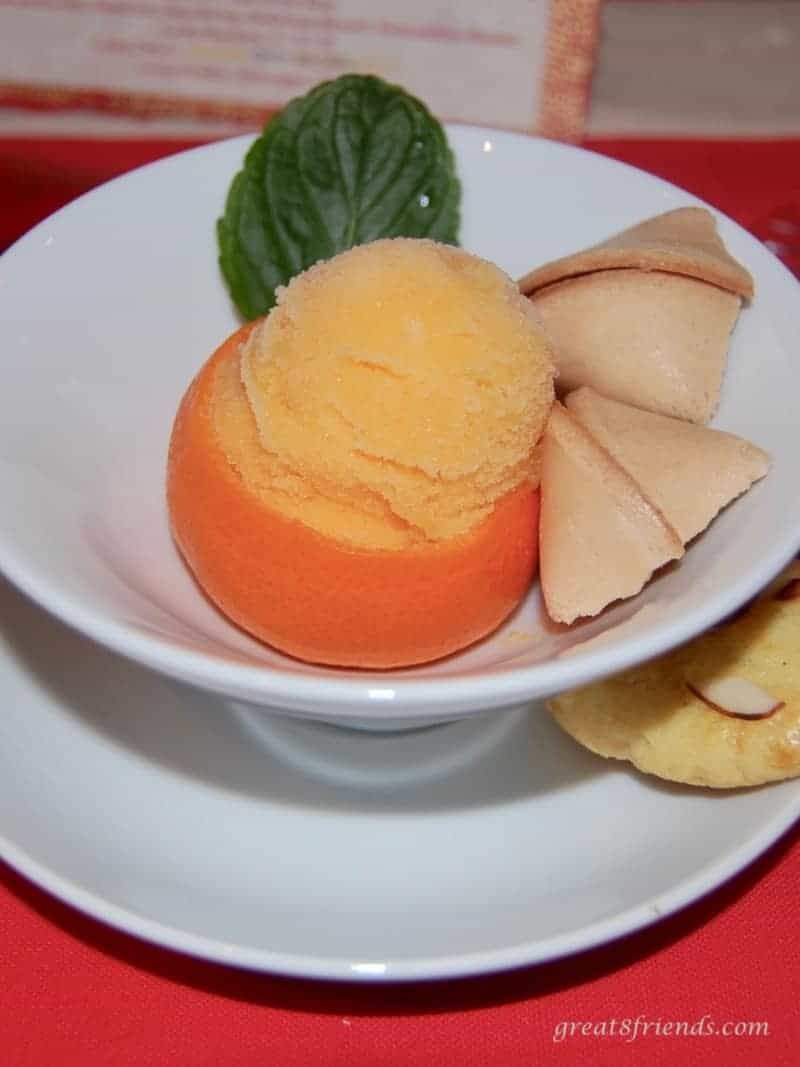 A scoop of tangerine sorbet in a tangerine shell with a fortune cookie and a leaf.