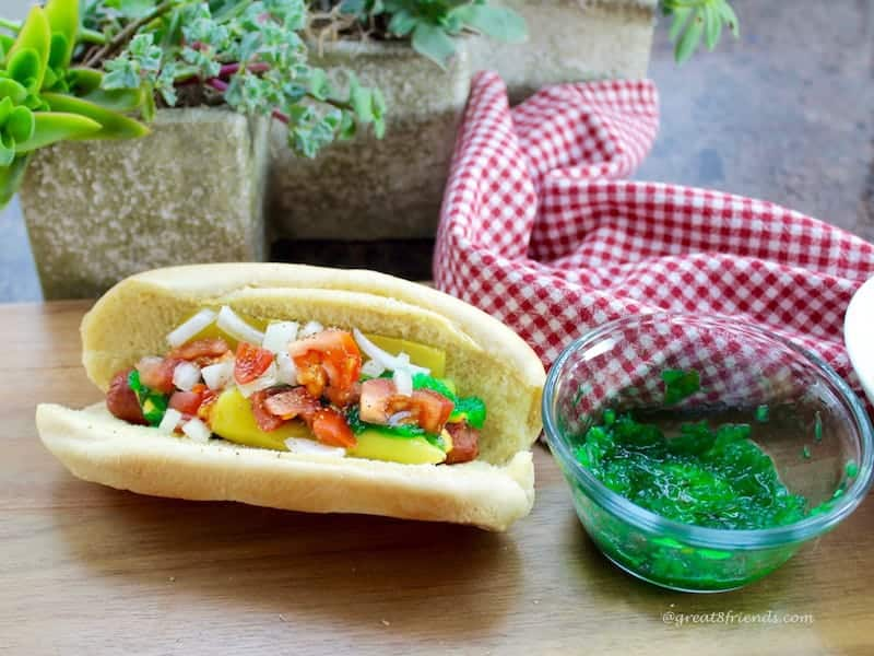A fully loaded hot dog, Chicago style next to a bowl of bright green relish.